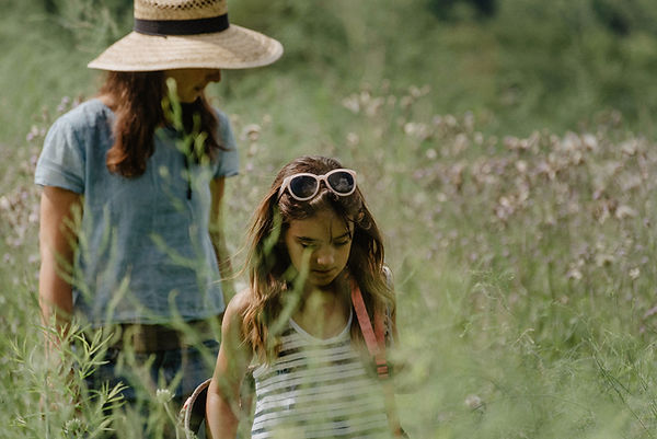 Woman in hat and girl in sunglasses walking in a field