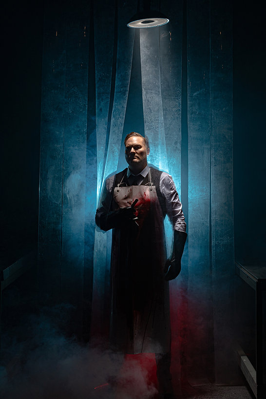 A theatrical picture by Roc Photography of actor Chris Crowe in the musical Sweeney Todd by WITCH Music Theatre at Te Auaha. He is holding a razor with a bloody apron.