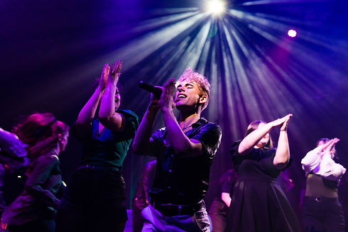 A theatrical picture by Roc Photography of actor Jared Pallesen singing in the musical theatre concert underscore_ at Te Auaha by WITCH Music Theatre. He is mid song and is holding a microphone with an ensemble of dancers behind him.