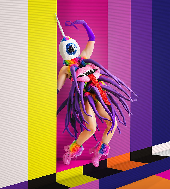 An image of The Purple People Eater Pop Concert character by CubaDupa posing in costume with tentacles, glitter and high pink boots. They are posing on a static TV background design. Produced by WITCH Music Theatre.