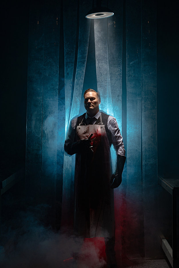 A theatrical picture by Roc Photography of actor Chris Crowe playing Sweeney Todd in the musical of the same name. He is holding a razor and is wearing a bloody apron.