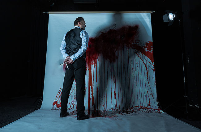 A theatrical picture by Roc Photography of Chris Crowe playing Sweeney Todd in the musical of the same name. He is holding a razor and is standing on a white sheet of paper covered in blood.