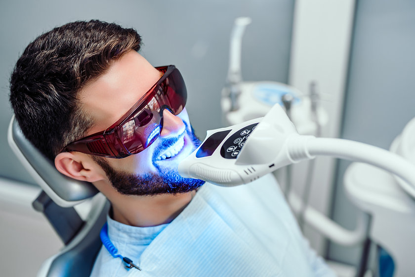 Dentist starting teeth whitening procedu