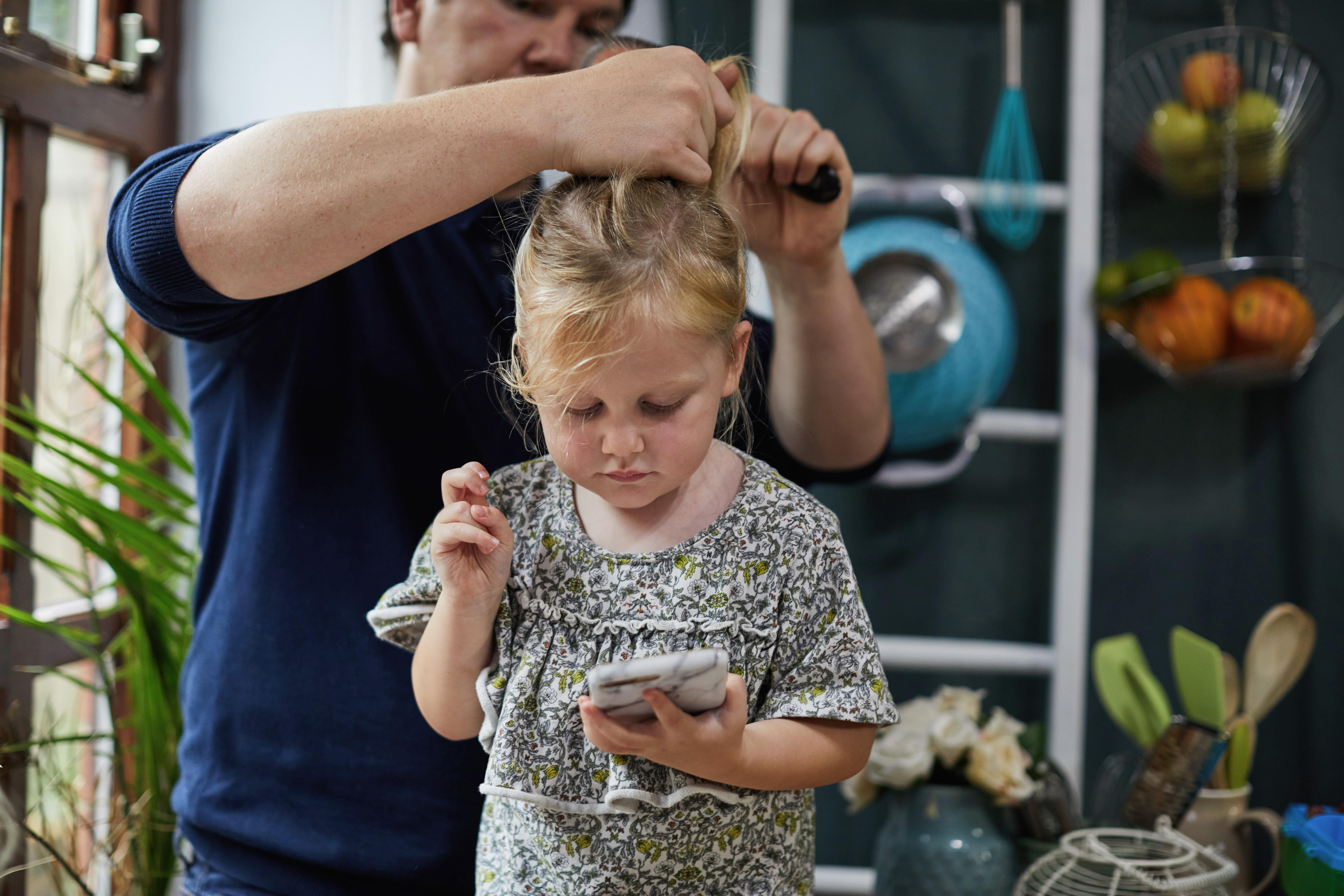 Padre peinando el cabello de la hija