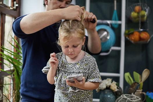 Vater kämmt das Haar der Tochter
