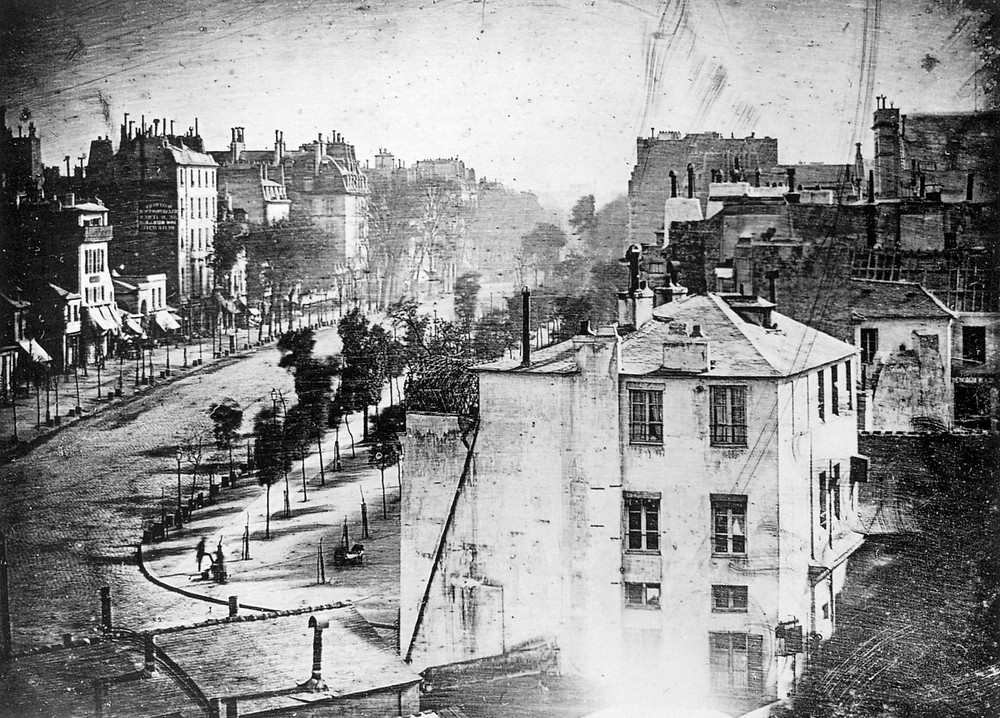 The Boulevard du Temple, Daguerre 1839. A lone man is recorded during the long exposure of the busy boulevard all because he is standing still whilst his boots are shined.