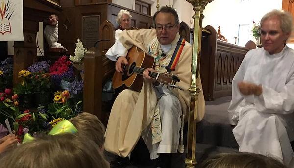 Rev. Herbert Jones plays guitar during his children's sermon one Sunday morning.