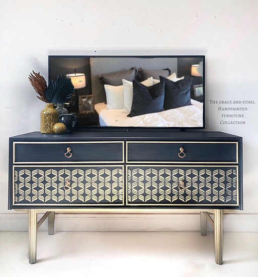a front view of a mid century modern dressing table with large mirrior and 4 drawers with a gold stencil design