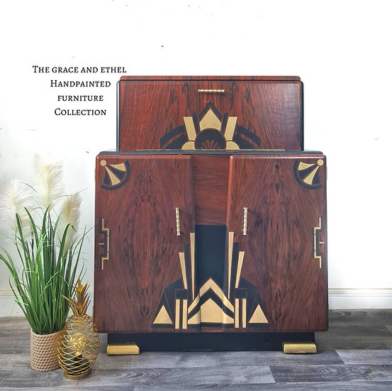 A front view of the art deco drinks cabinet showing the art deco stencil design and the natural wood door fronts