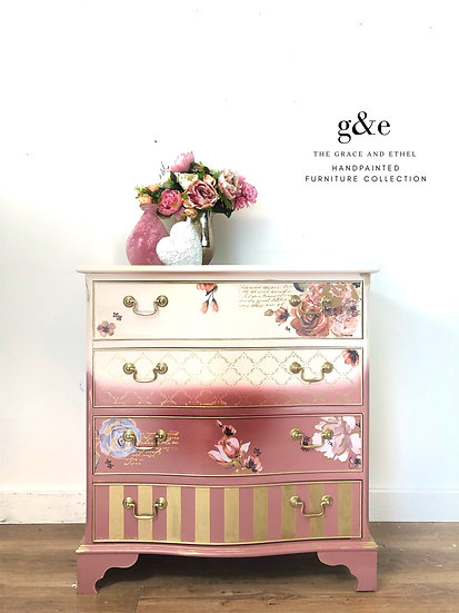 a two tone pink chest of drawers with gold strips and floral design