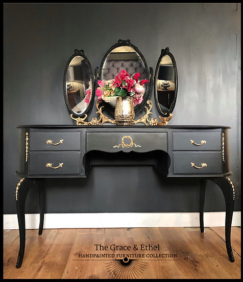 a front view of a black and gold french louis dressing table with a oval triple mirror