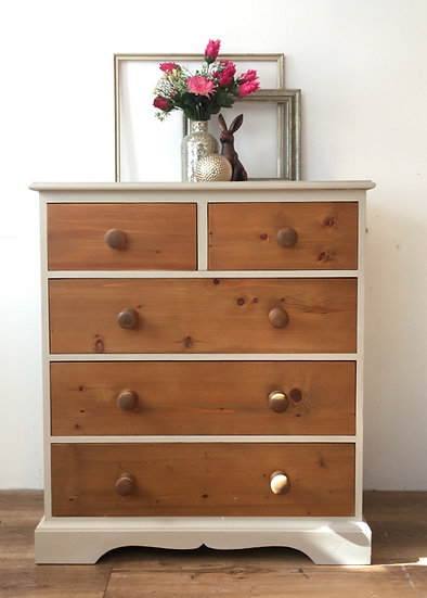 a set of solid pine drawers the extrerior is painted in a beige taupe colour with natural wooden drawers