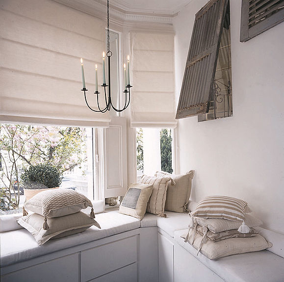 At home with white. Easy elegance. Comfortable interiors. White & fresh living. Serene interiors. White interior. Window seat with white upholstered cushions. White silk roman blinds. Cream cushions. Iron candelabra. Rise & fall concealed workstation. Provencal salvage grey shutters