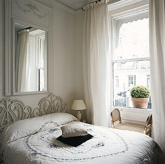 White bedroom. White French silk curtains. Period gilt bench. Cream Wedgwood lamp with silk shade. Cream & black bedspread. French vintage wall mirror.