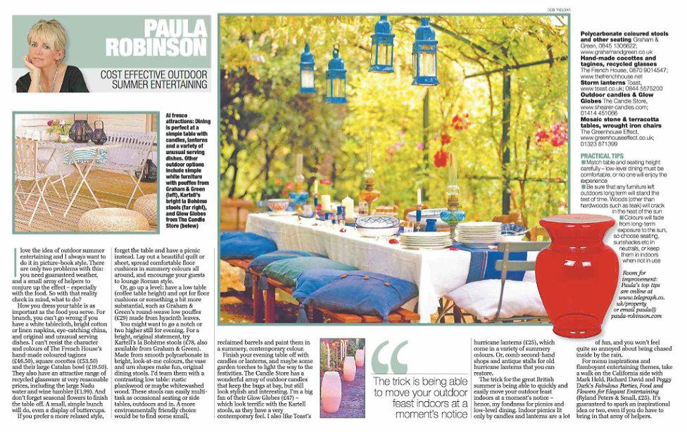 Cost Effective Outdoor Summer Entertaining. Paula Robinson Rossouw Sunday Telegraph column. The Room Planner. Blue lanterns. Outdoor table with tablecloth and cushions. Cream candle lamps. Red garden urn seat