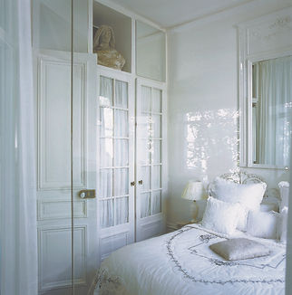 At home with white. White bedrooms. Romantic bedrooms. Parisian bedrooms. White & fresh living. Living Parisian style. Luxurious French living. Calm & neutral interiors. Bedroom chic. Floor-to-ceiling glass wall dividing a bedroom and living room. White bedroom. Vintage French glazed doors used for closet doors. Curved French double doors with original ironmongery. White lace cushions