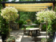 Container gardening with architectural salvage. Outdoor rooms. Inspirational terraces. Gardening with light & colour. Outdoor living. Coastal style. Country living. Country style. At home in the garden. Serene outdoor spaces. Relaxing outdoor living. Outdoor dining. Large stone terrace at Rocky Pastures with canvas pergola and container pots. Architectural salvage table and bench. Dappled willow trees.