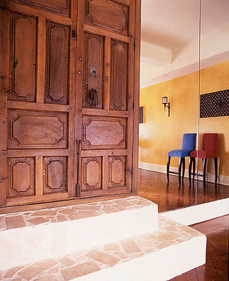 Spanish wooden doors and stone steps. Floor-to-ceiling mirror. Velvet bar stools. French balcony gratings converted to wall lights