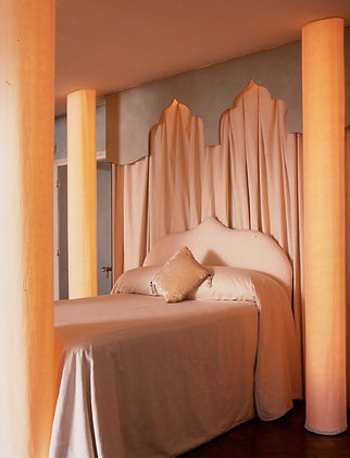 Serene settings. Relaxing interiors. Romantic bedrooms. Easy elegance. Contemporary Venetian interiors. Clean & minimal living. Luxurious bedrooms. Boudoir. Calm & neutral interiors. Cream bespoke fabric column bed. Internally-lit fabric columns. Cream headboard and velvet cushion. Four poster.