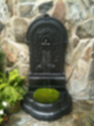 Antique cast iron wall fountain with moss ball on the stone terrace at Rocky Pastures