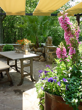 Stylish & original container gardening. Gardening with colour & light. Outdoor entertaining. Creating shade in a sunny spot. Creating an elegant terrace. Architectural salvage table and bench under canvas pergola on the stone terrace at Rocky Pastures. Copper architectual salvage pot planted with flowering plants