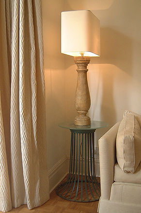 Recycled home. Easy elegance. Cream & fresh living. Serene interiors. Fun interiors. Calm & neutral interiors. French vintage street bin converted to side table with sandblasted glass to. Stone column lamp with rectangular shade. Cream sitting room/snug. Cream patterned curtains. Cream sofa.
