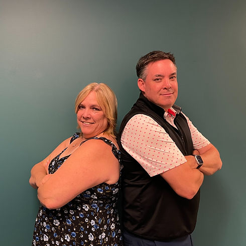 A picture of Shawn McNamara and Brenda Tait, the team of advisors of The Small Business Centre, standing back to back.