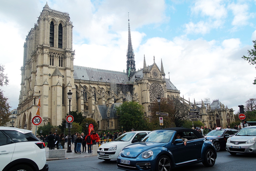 View of Notre Dame from across the street. Traffic on the street in front.