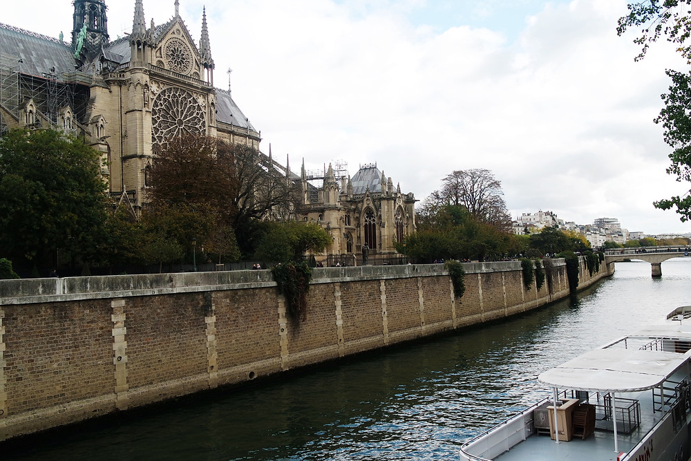 View of the rear of Notre Dame from across the river. A flat boat is moored in the bottom right.