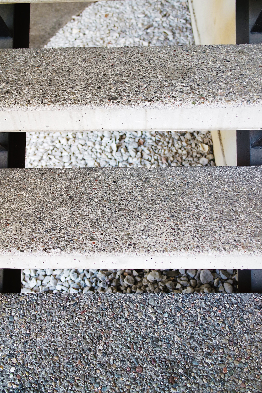 Three treads of a stone staircase, with open space in between each tread.