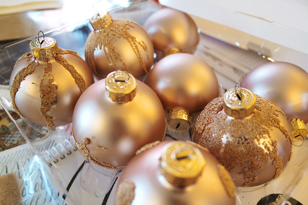 A clear plastic shell holding five gold glass balls decorated with micro beads and three plain gold glass balls.