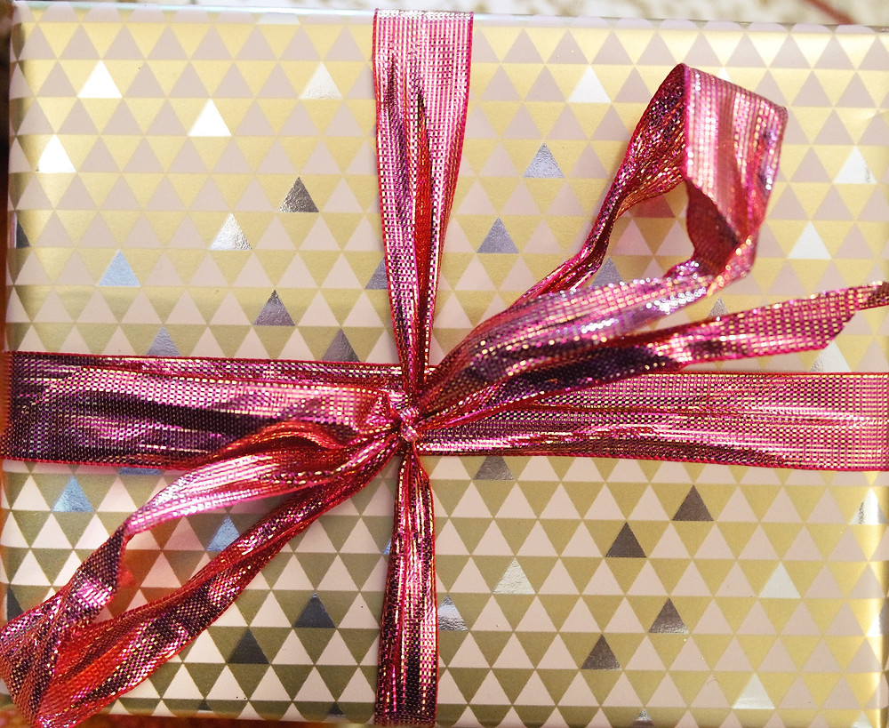 Pink metallic paper with a pattern of small triangles and a metallic pink ribbon.