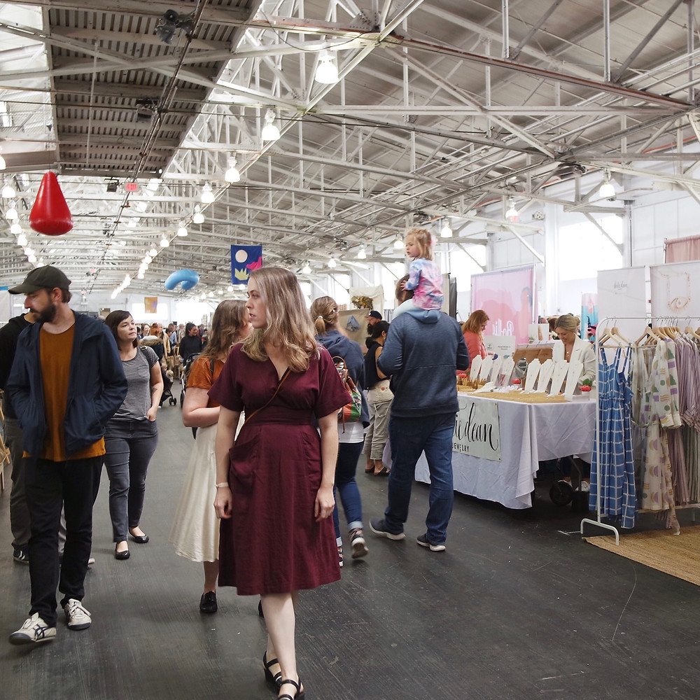 A woman in a burgundy wrap dress with short sleeves and black sandals walking through the Festival Hall at Fort Mason looking at booths during the Renegade Craft Fair.
