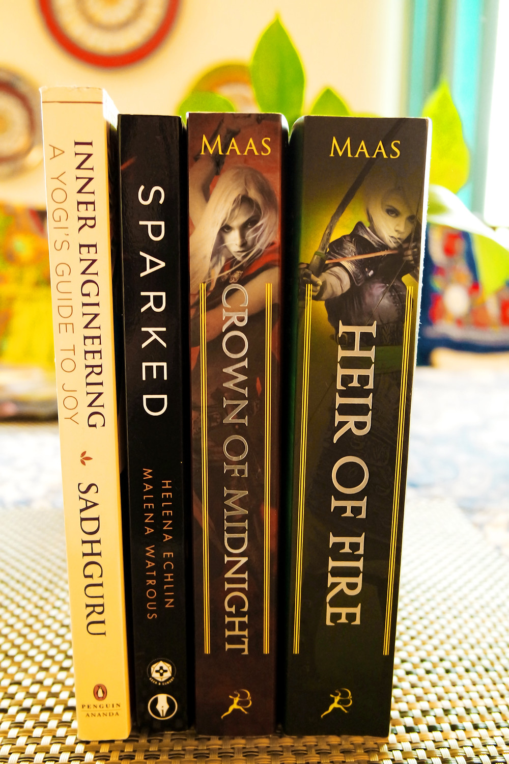Four books - Inner Engineering, A Yogi's Guide to Joy, Sparked, Crown of Midnight, and Heir of Fire