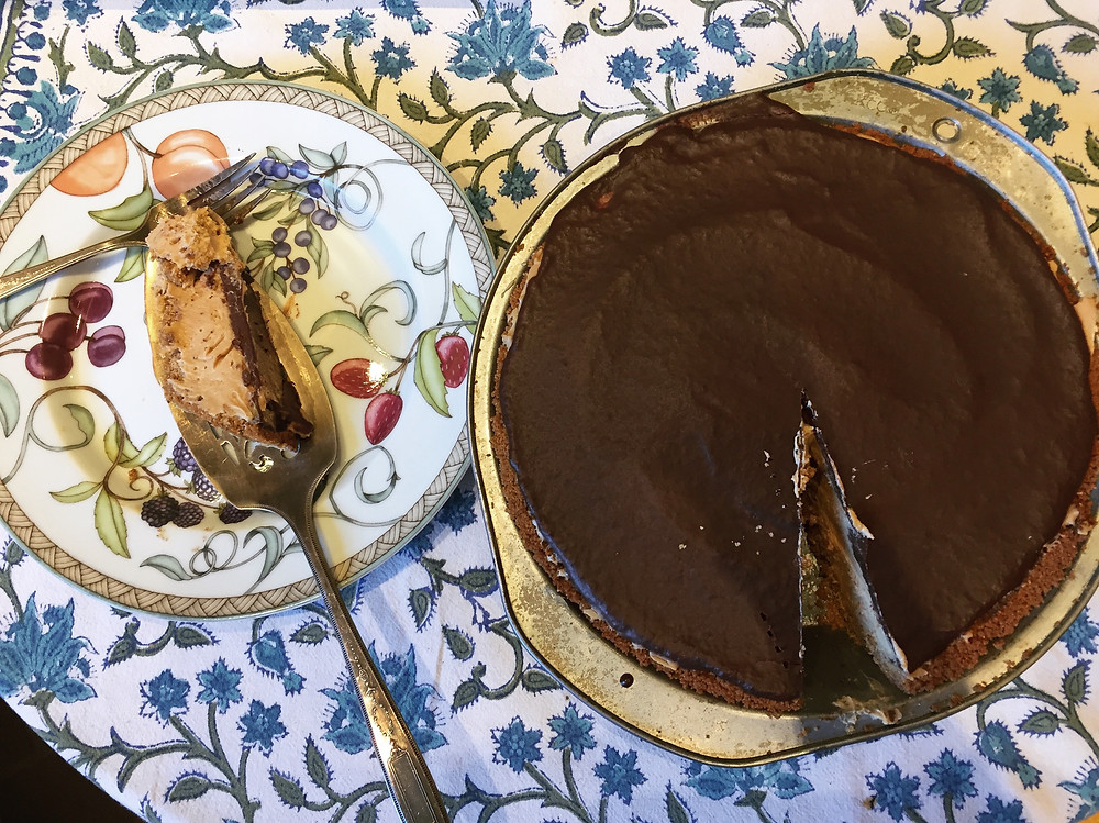 Chocolate Peanut Butter Pie in a silver pie tin sitting next to a plate with one pie slice, against a blue and white tablecloth.