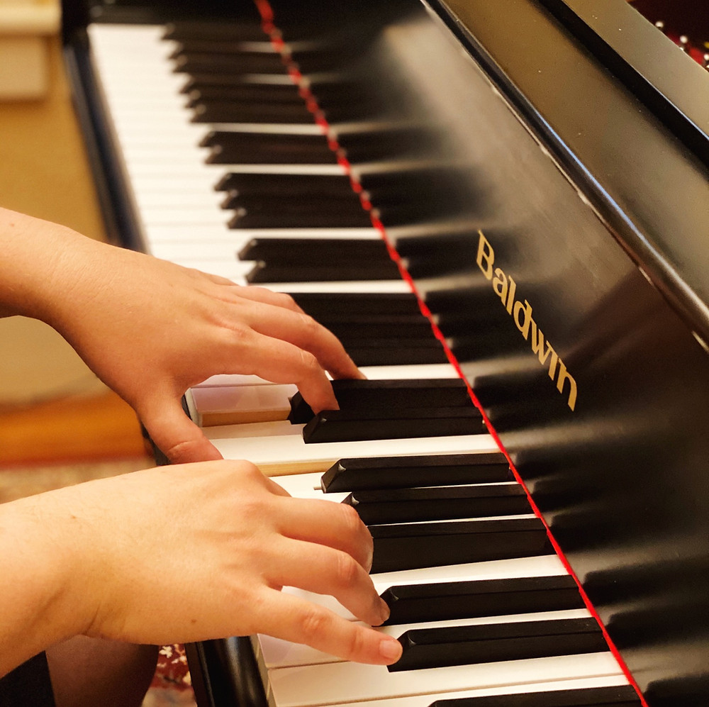 "Two hands are poised on the keyboard of a piano. The piano is black with a gold label that says ""Baldwin""."