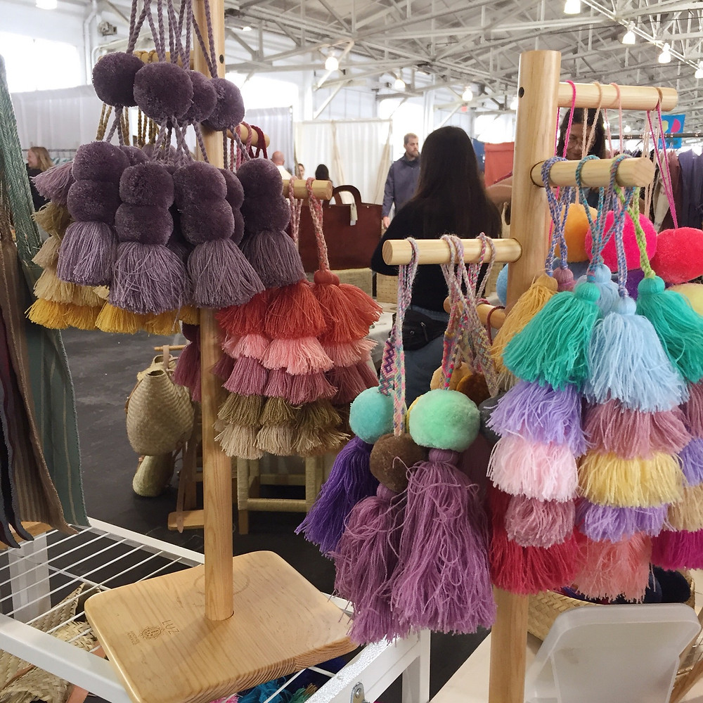 Wooden stands filled with tassels and pompoms in all colors - purples, yellow, red, pink, green, blue.