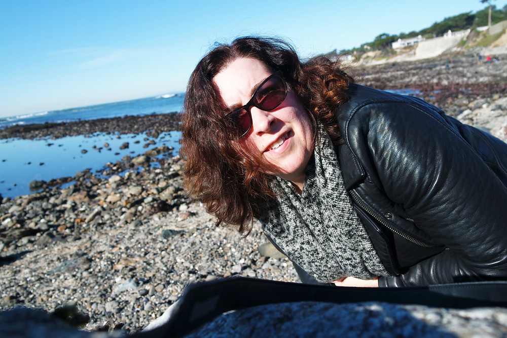 Sophia Dunkin-Hubby crouched down and looking at the camera, wearing sunglasses, a textured gray scarf and a black leather jacket, with the beach of Fitzgerald Marine Reserve in the background.