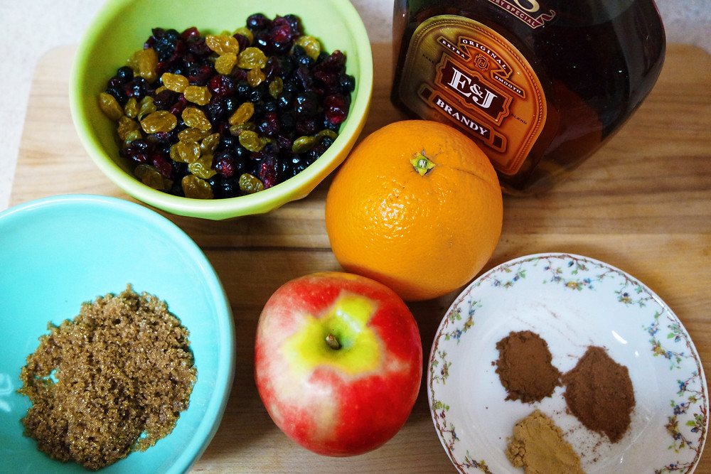 Mince pie filling ingredients, a bowl of brown sugar, a bowl of golden raisins, dried cranberries, and dried blueberries, an orange, an apple, a small dish of ground cinnamon, ginger, and nutmeg, and a bottle of brandy.