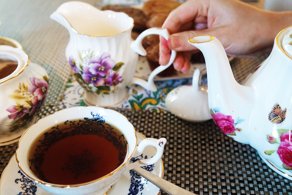 Blue and white pattern tea cup with tea in the foreground and a hand reaching for the creamer, white with purple flowers.