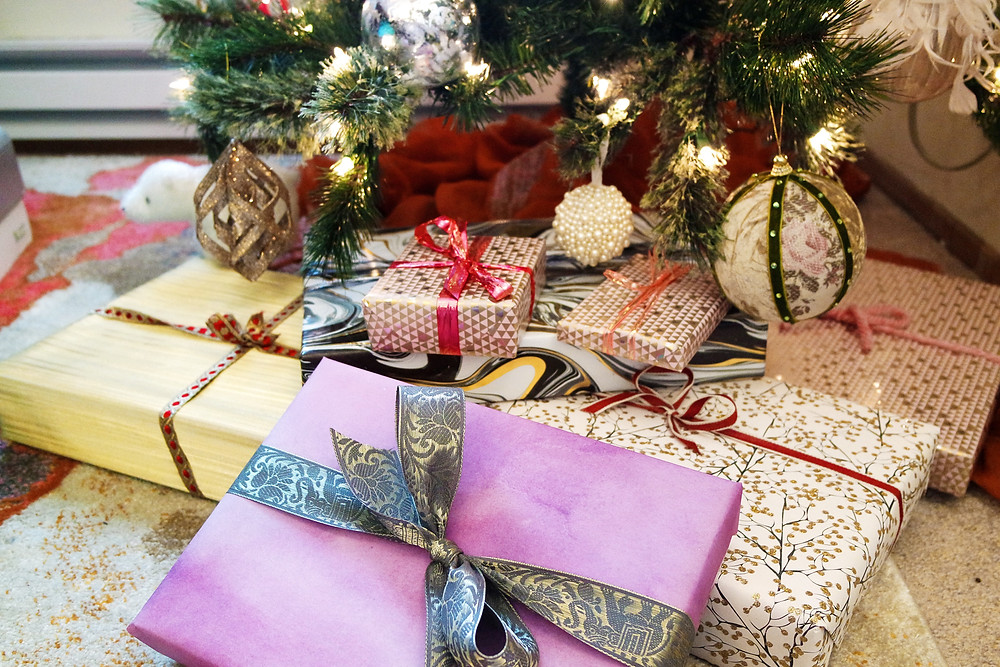 Gifts wrapped in different colored wrapping paper under a christmas tree - gold with gold and red ribbon, purple watercolor with gray satin ribbon, black and gold branches on white, with red and white ribbon, black, gold, and white marbled paper with silver ribbon, and soft pink with silver triangles and pink ribbon.