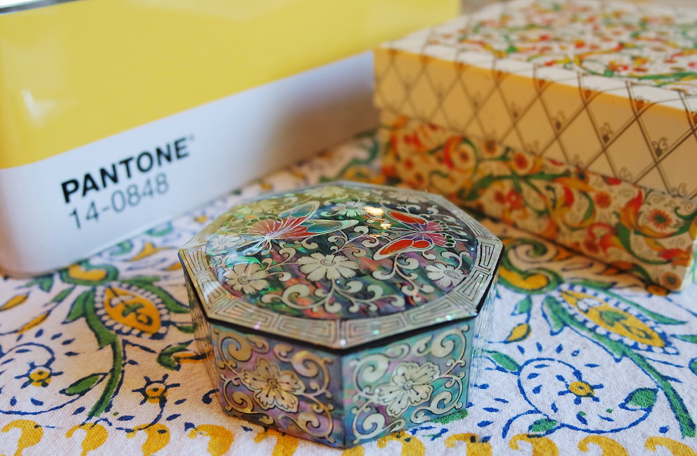 Three boxes - a yellow Pantone Tin, a box wrapped in Venetian paper in red, green, and gold on a cream background, and a octagonal, enamel box in green, white, and black with an iridescent finish.