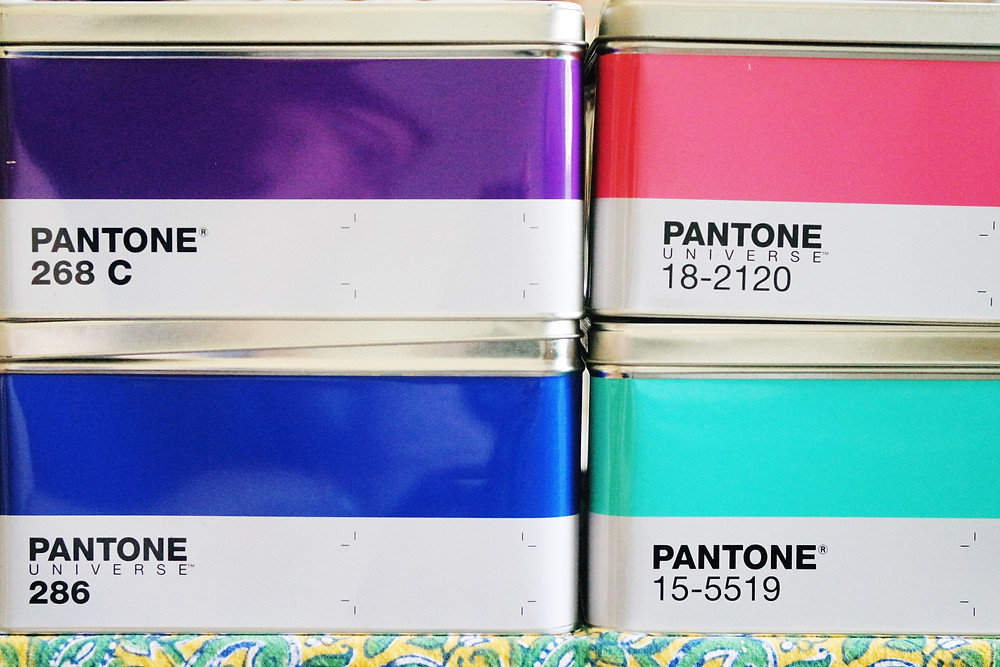 A stack of four pantone tins - purple, pink, blue, and cyan.