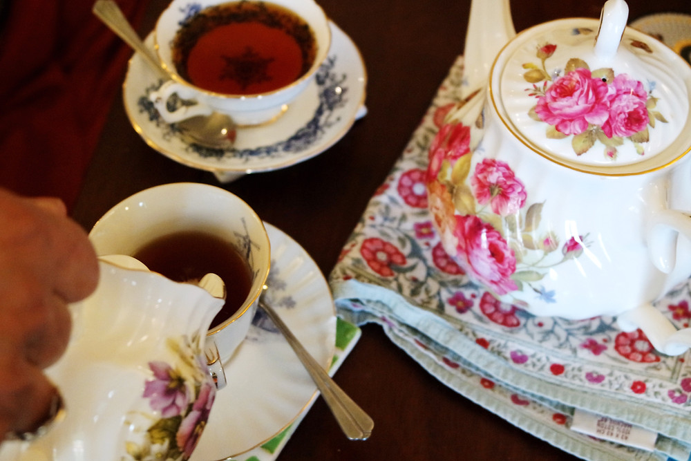 Flowered tea pot sitting on a floral napkin next to two cups of tea, one of which is having milk poured into it.
