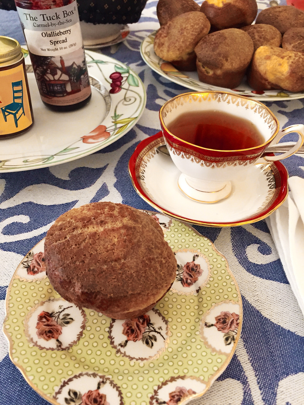 A small plate with a popover in the foreground next to a cup of tea, a plate with two jars of jam on it, and a plate of popovers sitting on a blue and white tablecloth.