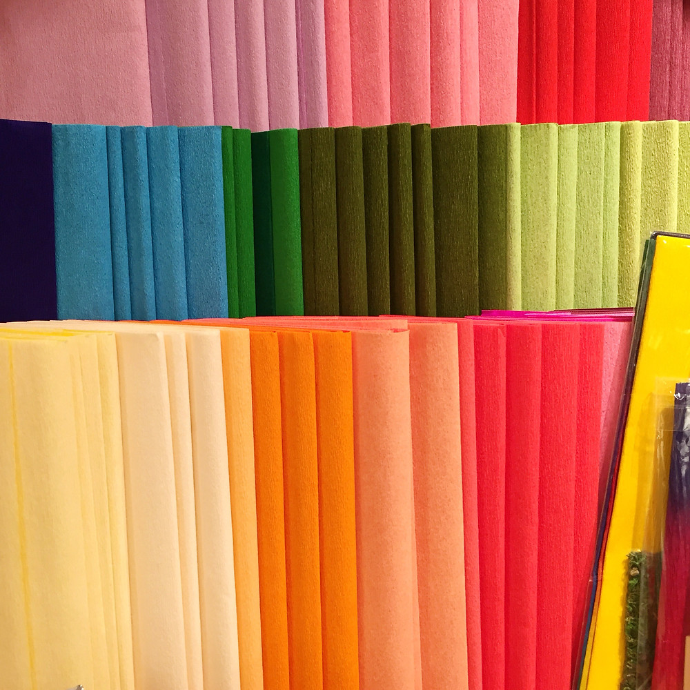Sheaves of crepe paper in all different colors - pinks, reds, blues, greens, yellows and oranges - arranged in three rows on a shelf.