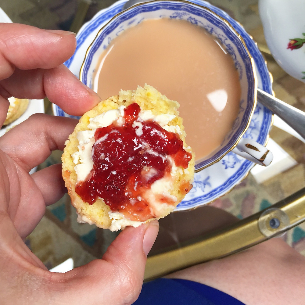 Half a scone spread with clotted cream and strawberry jam held over a cup of milky tea in a blue and white china cup.