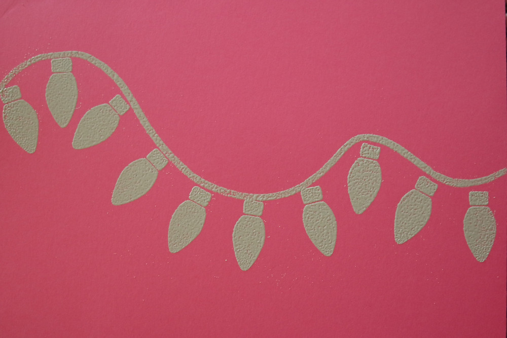 Hot pink card with a strand of Christmas lights all in white.