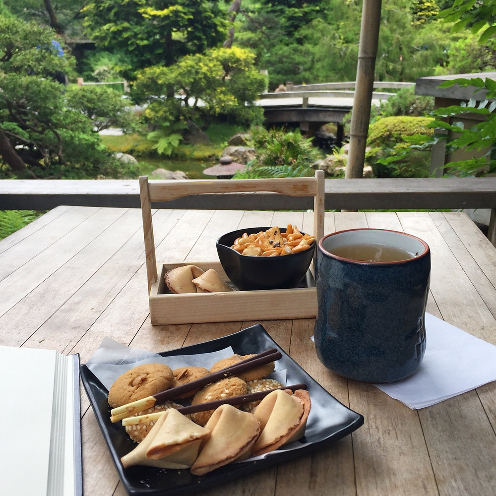 Wooden table next to a railing overlooking a pond with bridge over it at the San Francisco Japanese Tea Gardens. On the table is a mug of Jasmine Tea, a small wooden tray with handle holding a black bowl of savory orange crackers and two fortune cookies, and in the foreground the edge of a notebook and a black square dish holding nine cookies (sesame, almond, and fortune), and three chocolate covered pocky sticks.