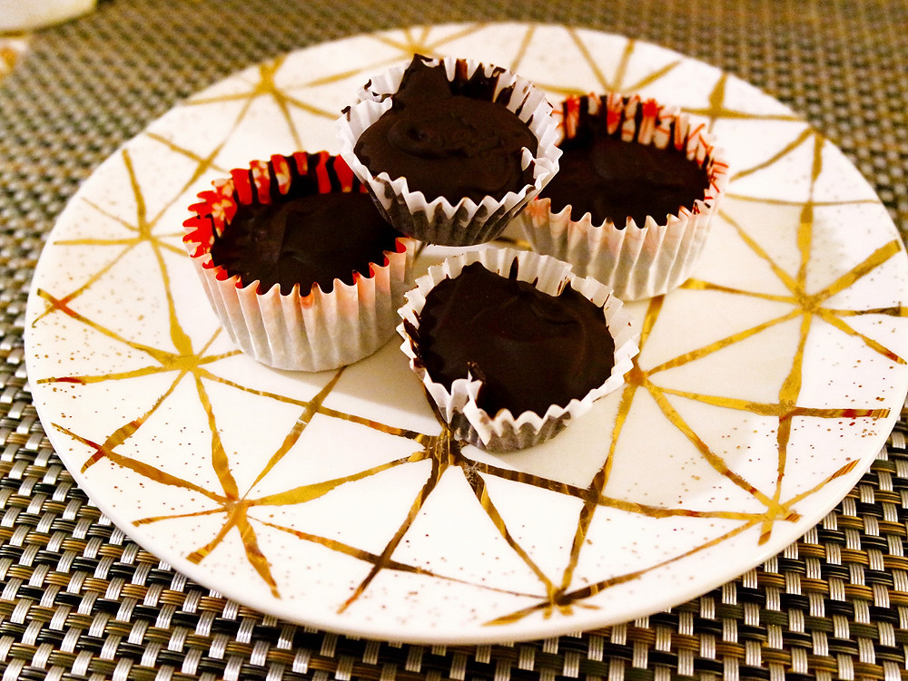 A white plate with gold metallic lines (squares crossed with diagonal lines) with 4 small Chocolate Peanut Butter Cups on it.